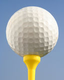 Golfball against blue sky. Golfball on yellow tee against blue sky Royalty Free Stock Photo