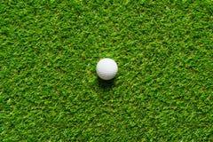 Golfball auf Beschaffenheit des grünen Grases des Golfplatzes für Hintergrund stockfotografie