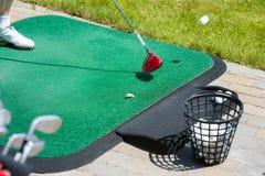 Golfball auf dem Grün und dem Putter Stockbild