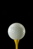 Golfball auf gelbem T-Stück Lizenzfreie Stockbilder