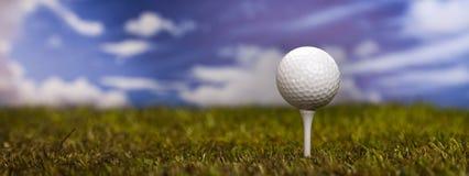 Golfball auf grünem Gras über einem blauen Himmel Lizenzfreies Stockfoto