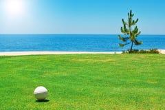 Golfball auf grünem Gras mit dem Ozean. lizenzfreie stockfotografie