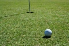 Golfball auf grünem nahem Loch Lizenzfreies Stockbild