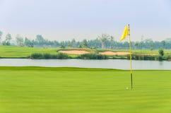 Golfball auf grünem nahem Loch mit gelber Markierungsfahne Lizenzfreies Stockfoto