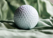 Golfball auf grünem silk Hintergrund Lizenzfreie Stockfotografie