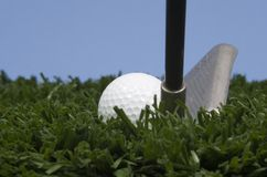 Golfball auf Gras mit Golfclub gegen blauen Himmel Lizenzfreie Stockbilder