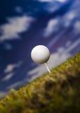 Golfball auf grünem Gras über einem blauen Himmel Lizenzfreie Stockfotografie