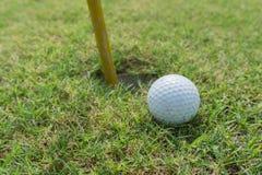 Golfball auf Lippe der Schale oder des Lochs stockfoto