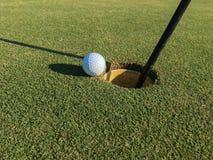 Golfball auf Rand des Loches Stockfotografie