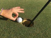 Golfball auf Rand des Loches Stockfotos