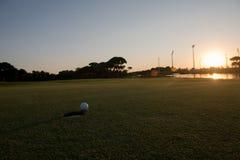 Golfball auf Rand des Lochs Stockfoto