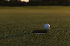 Golfball auf Rand des Lochs Lizenzfreies Stockbild