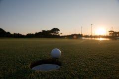 Golfball auf Rand des Lochs Lizenzfreie Stockfotos