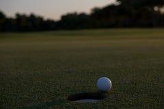 Golfball auf Rand des Lochs Lizenzfreies Stockfoto