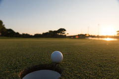 Golfball auf Rand des Lochs Stockbilder