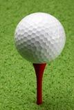 Golfball auf rotem T-Stück Stockfotografie