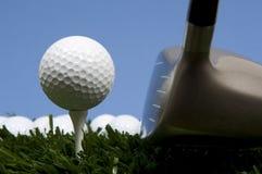 Golfball auf T-Stück auf Gras mit Treiber Stockbild