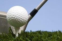 Golfball auf T-Stück auf Gras mit Treiber Lizenzfreie Stockfotos