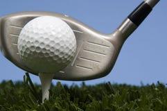 Golfball auf T-Stück auf Gras mit Treiber Stockbilder