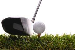 Golfball auf T-Stück im Gras mit Treiber Stockbild