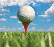 Golfball auf T-Stück im Gras. Nahaufnahme, angesehen von der Bodenhöhe. Stockbilder