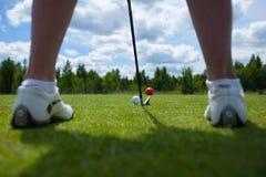 Golfball auf T-Stück und Golfclub auf Golfplatz stockbild
