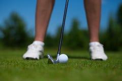 Golfball auf T-Stück und Golfclub auf Golfplatz lizenzfreie stockfotos