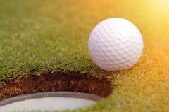 Golfball bijna in het gat Stock Afbeelding