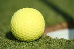 Golfball at Cup. Golfball at the edge of the cup, with a shadow on the blurred grass in the background. Horizontal framing Royalty Free Stock Images