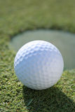 Golfball At Cup. Backlit golfball casting a long shadow on the green with hole blurred in background. Vertical framing Royalty Free Stock Photos