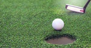 Golfball, der in das Loch fällt Stockfotos