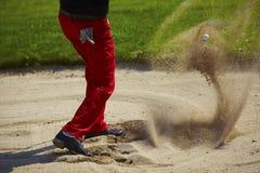 Golfball in der Luft im Bunker Stockbild