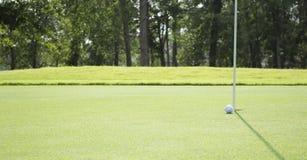 Golfball, der zum Loch auf Golfplatz rollt Lizenzfreie Stockfotografie