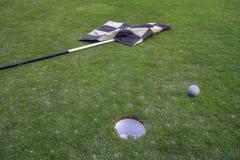 Golfball durch Hole Marker Flagstick Stockbilder