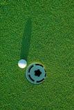 Golfball ein nahe bei Loch 3 Lizenzfreie Stockfotos