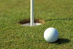 Golfball in front of the hole Stock Image