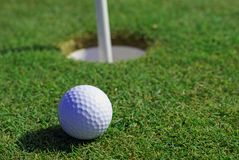 Golfball in front of the hole royalty free stock photos