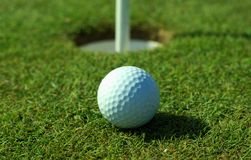Golfball in front of the hole Royalty Free Stock Photography