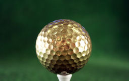 Golfball in gold Stock Images