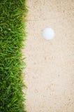 Golfball i sand Arkivbilder