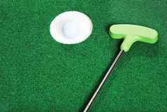 Golfball im Cup mit Putter Stockfotos