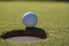 Golfball im Loch Stockfotografie