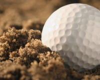 Golfball im Sand Stockfotografie