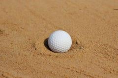 Golfball im Sand auf Bunker Stockbild