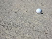 Golfball im Sand-Bunker Stockfotos