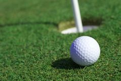 Golfball In Front Of The Hole Stock Photo