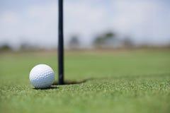 Golfball am Loch stockfotos