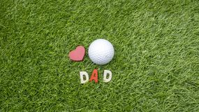 Golfball mit rotem Herzen und Wort VATI lizenzfreie stockbilder