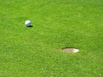 Golfball nahe bei dem Loch stockfotos