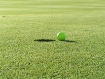 Golfball nahe bei Loch stockbild